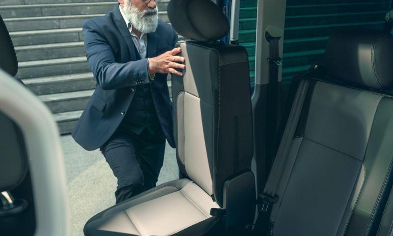 Ein Mann verstellt einen Sitz im Fahrgastraum eines Fahrzeugs.