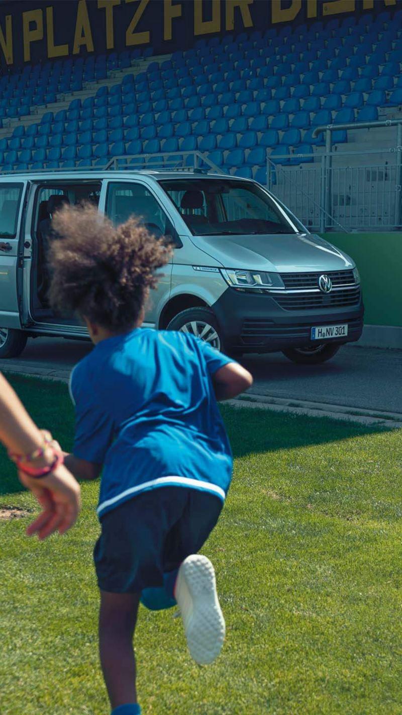Eine Horde Fußballspielerinnen läuft auf ihren Trainer am einem Volkswagen Caravelle zu.