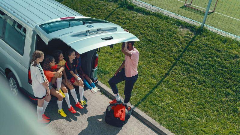 Einige Fußballerinnen sitzen im Kofferraum von einem Volkswagen Caravelle.