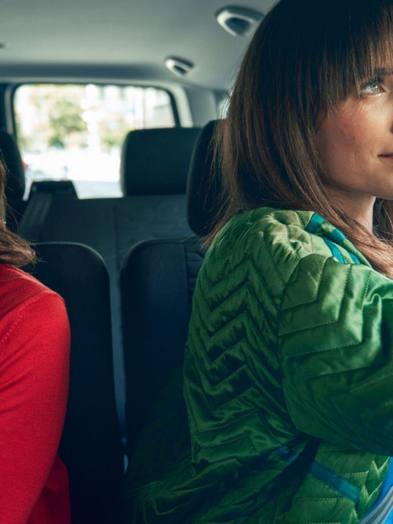 Zwei Frauen sitzen im Fahrgastraum der VW Caravelle 6.1.