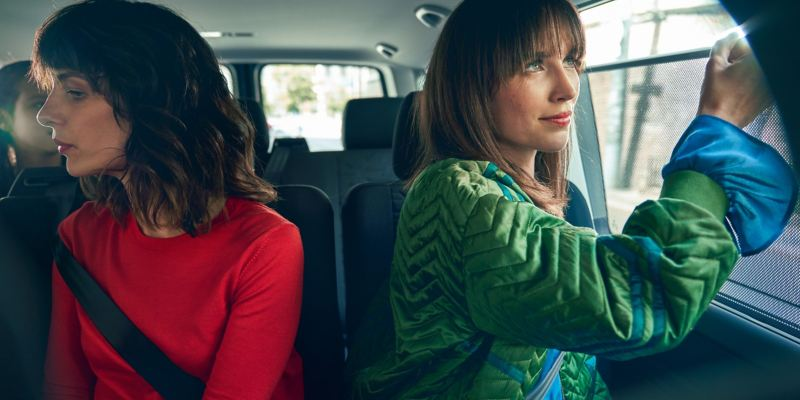 Two women are sitting the backseats of a VW Caravelle 6.1.