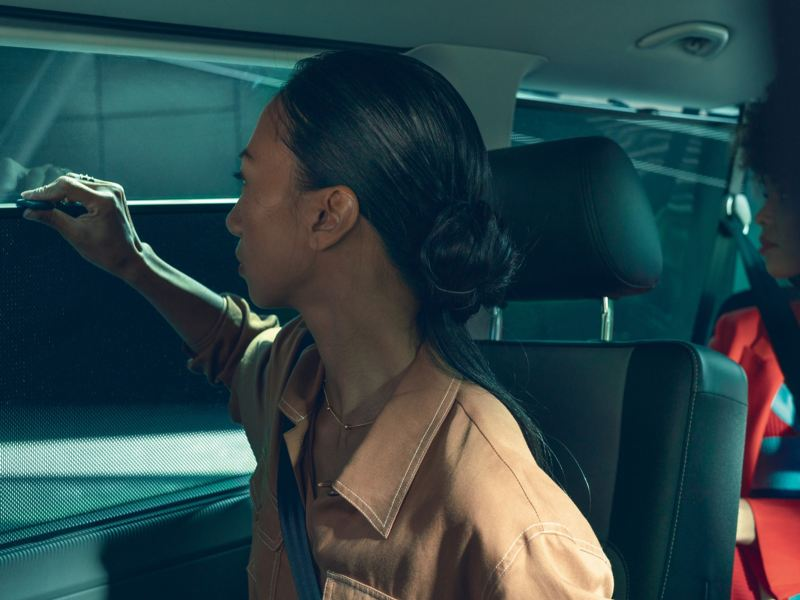 Kobieta obsługuje roletę wewnątrz pojazdu.