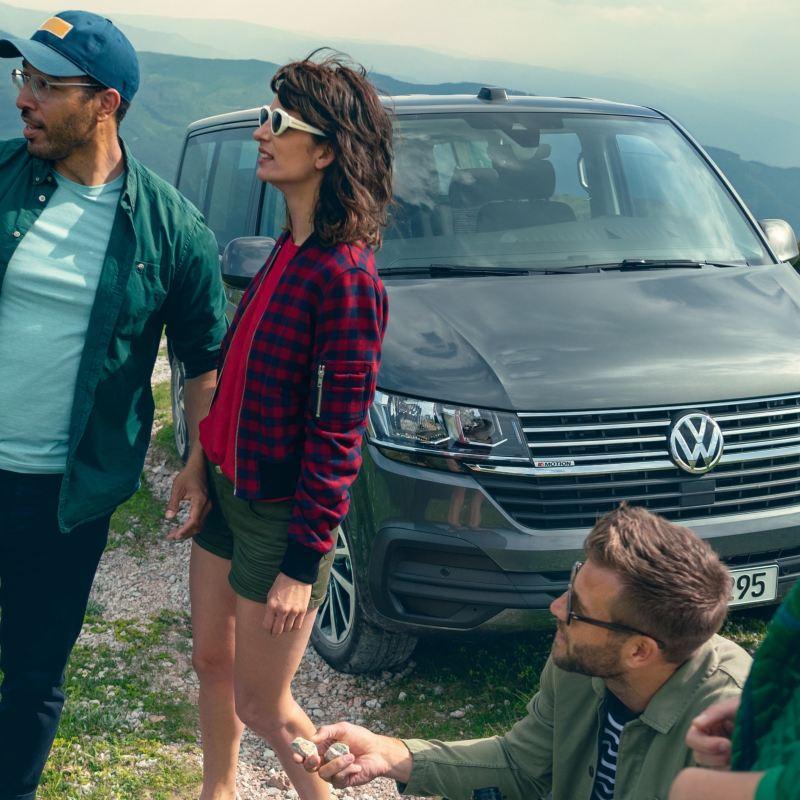 Tre ragazzi vicino a un VW Caravelle parcheggiato, vista frontale di 3/4.