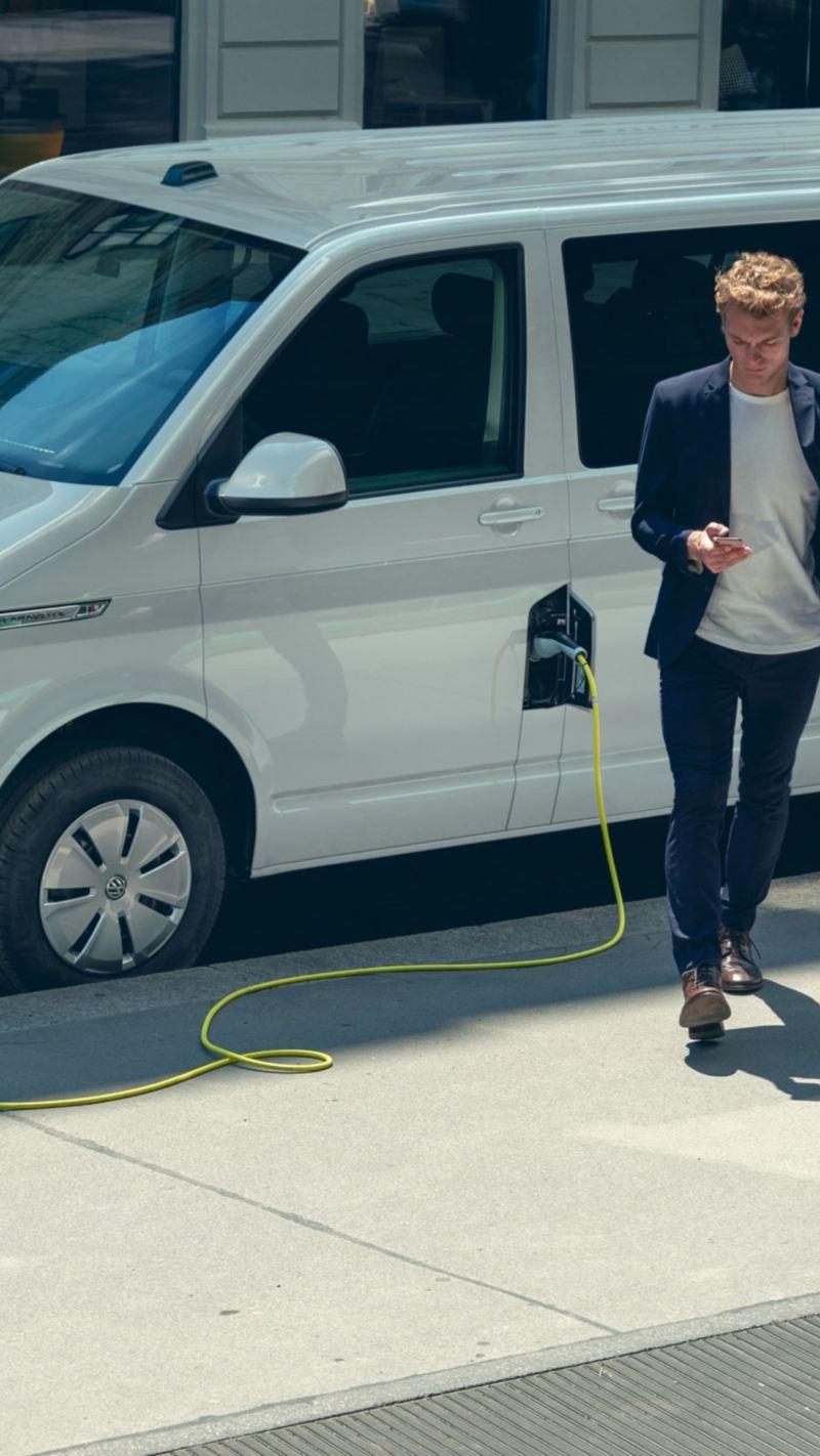 Un homme debout devant une ABT e-Caravelle en train d'être rechargée sur une borne de recharge.