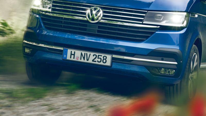 Dettaglio del paraurti e delle luci frontali di Caravelle Volkswagen su una strada di montagna.
