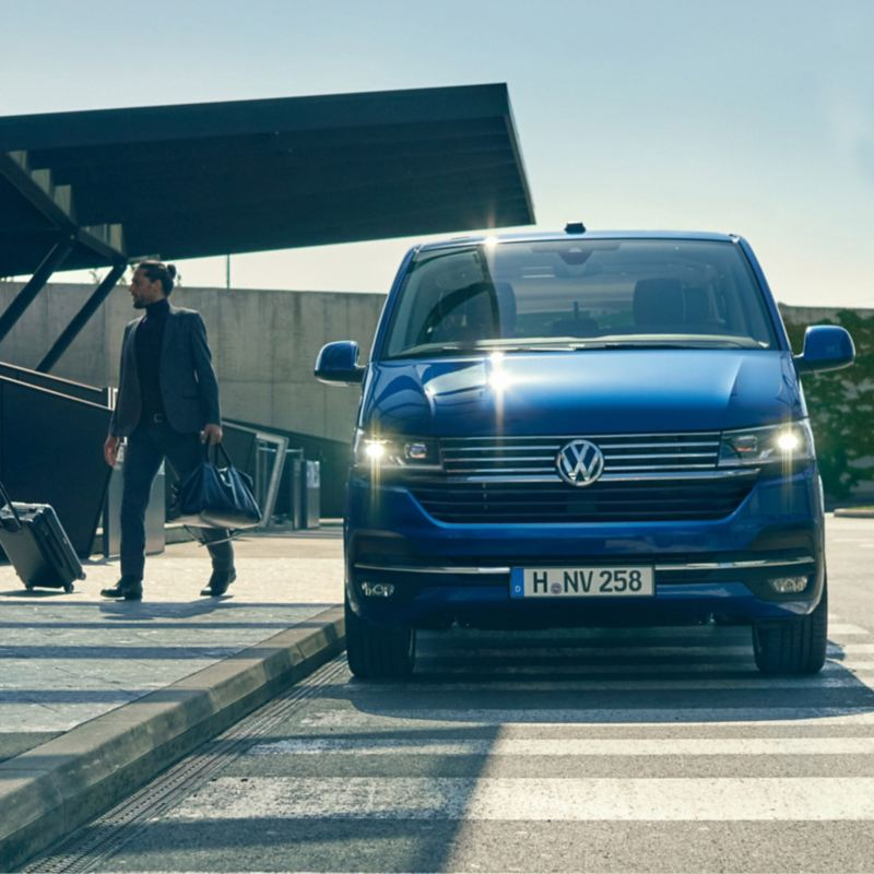 vw Volkswagen Caravelle varebil familiebil rullestolbil maxitaxi taxi persontransport hotell dame i skjørt går over veien mann i blå dress flyplass