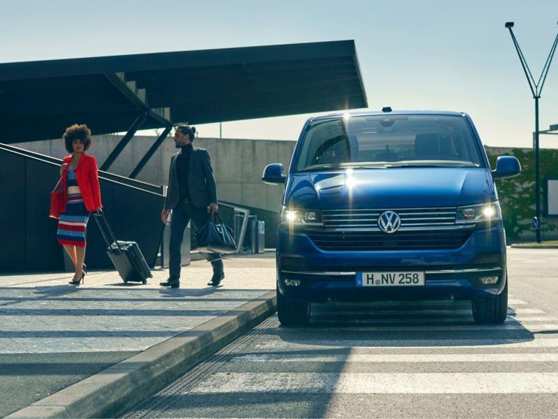 Bildet viser en blå Volkswagen Caravelle familiebil som fungerer som en maxitaxi for persontransport av mennesker til flyplass