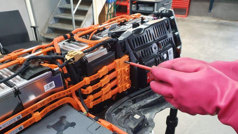 Reparasjon av elbil batteri med skrujern og gummi hansker VW Volkswagen