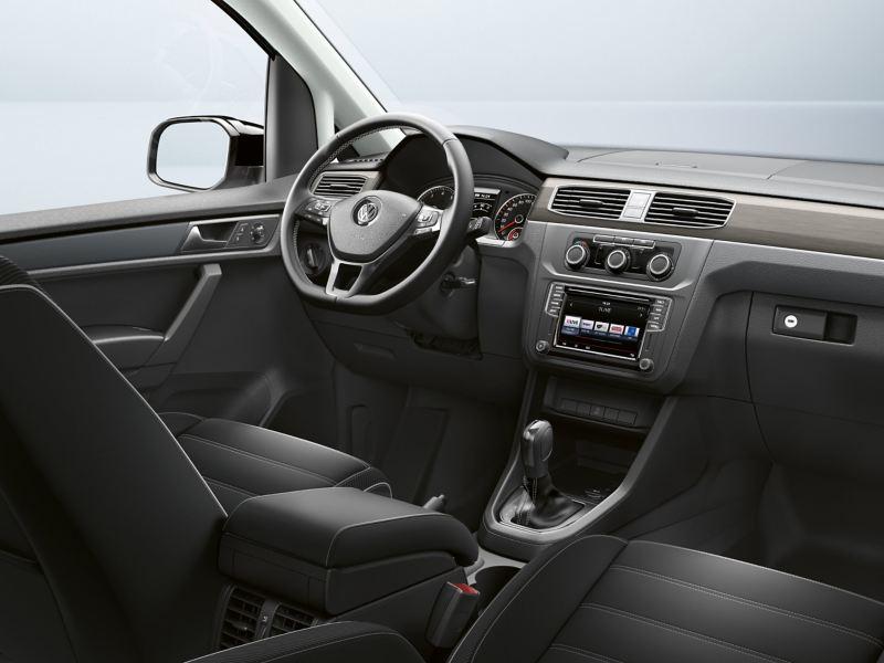 Widok z drugiego rzędu siedzeń na fotel kierowcy i wnętrze kabiny.
