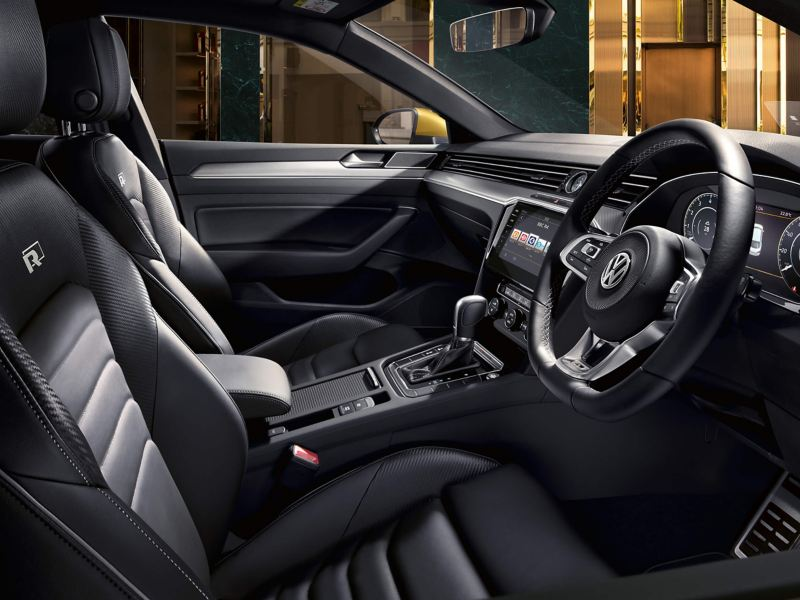 Front interior shot of a Volkswagen Arteon, city at night in outside,