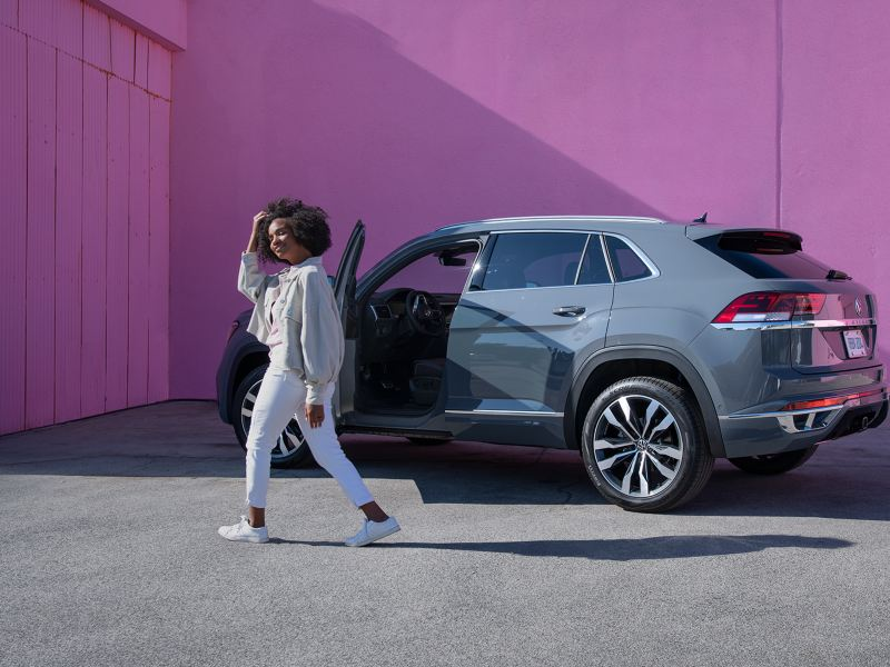 "Woman standing in front of VW Atlas Cross Sport SUV, link out to the ""be the change"" page"