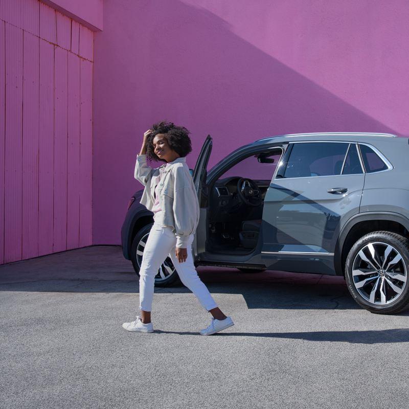 Woman standing in front of Atlas Cross Sport SUV