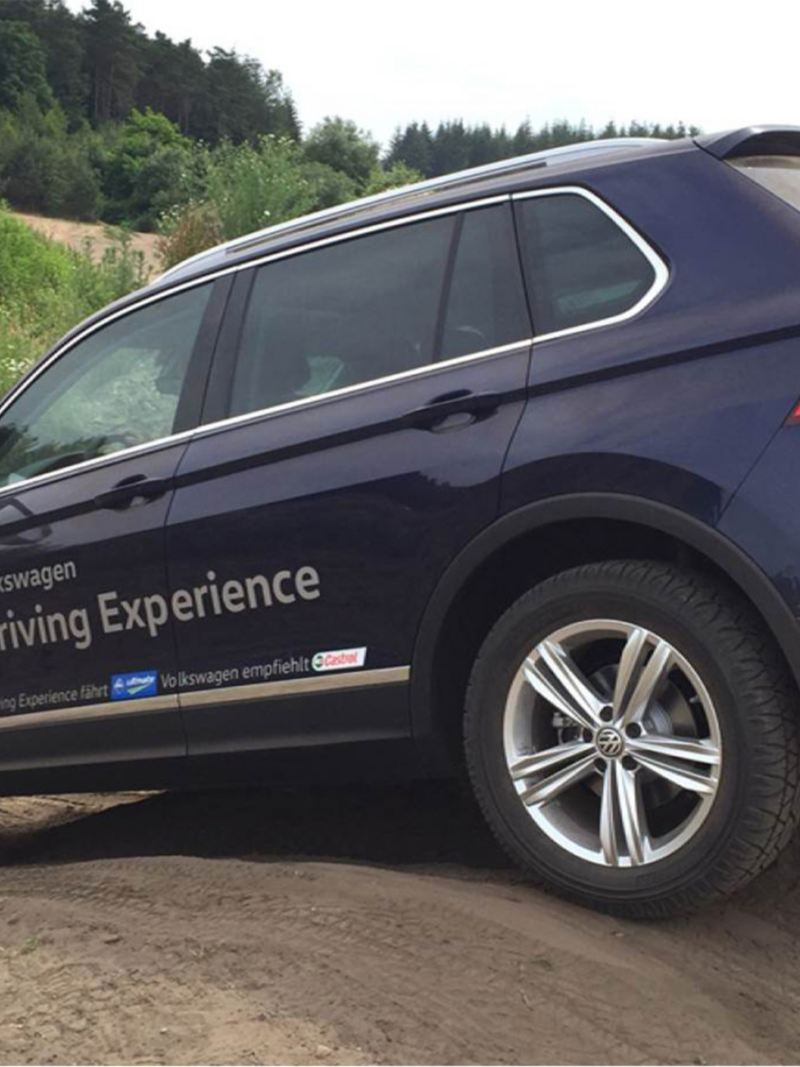 View of a Volkswagen Tiguan from behind and at an angle, driving over a hill on an unpaved road