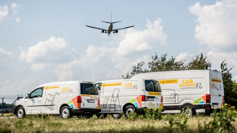 Caddy, Transporter i Crafter w okleinie o carsharingu stoją na polanie, nad nimi leci samolot