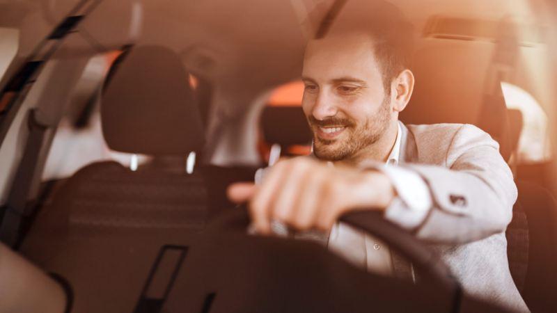 Conductor alegre al manejar su auto seminuevo garantizado de Volkswagen