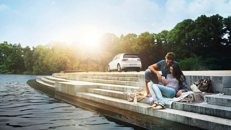 Couple with e-Golf sitting by a pond