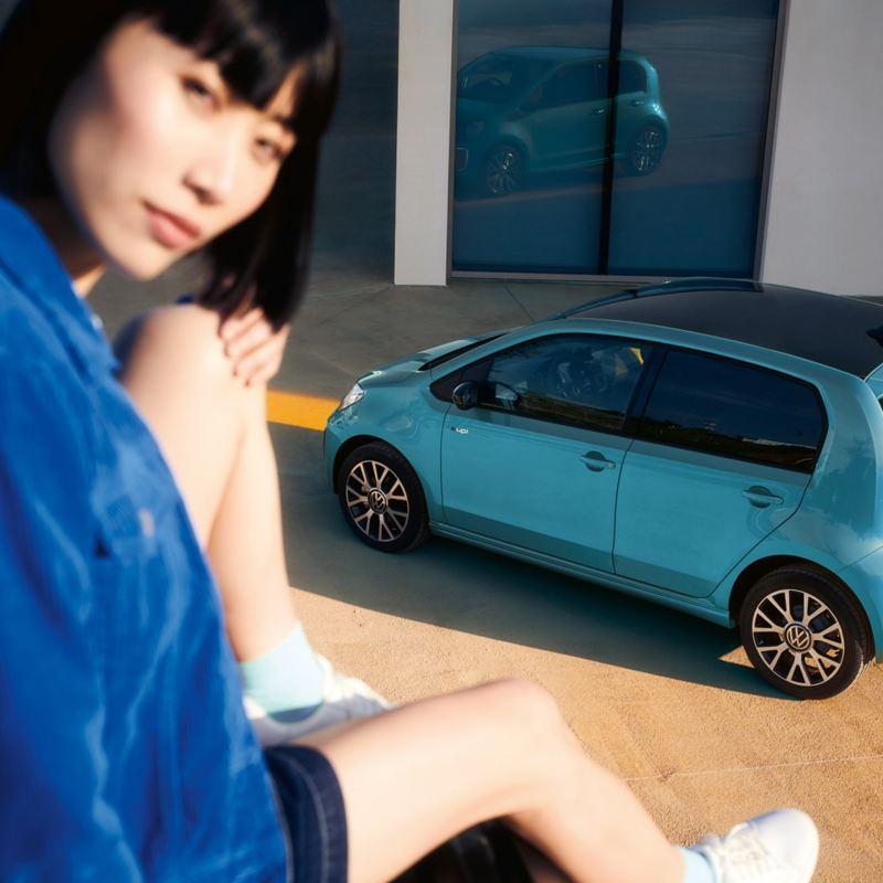 Eine Frau sitzt auf einer Mauer über einem geparkten e-up! und schaut in die Kamera