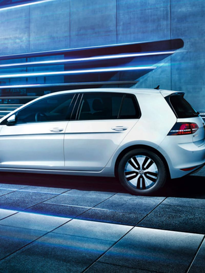 Profile shot of a white Volkswagen e-Golf, in an industrial setting..