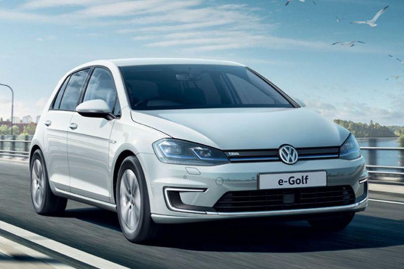 Front shot of a white Volkswagen e-Golf driving across a bridge.