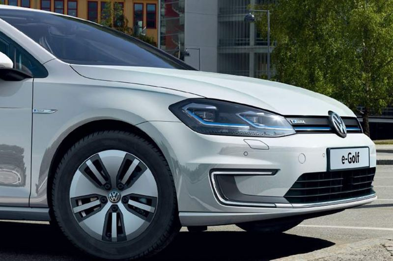 Front profile shot of a white Volkswagen e-Golf, charging in a carpark.