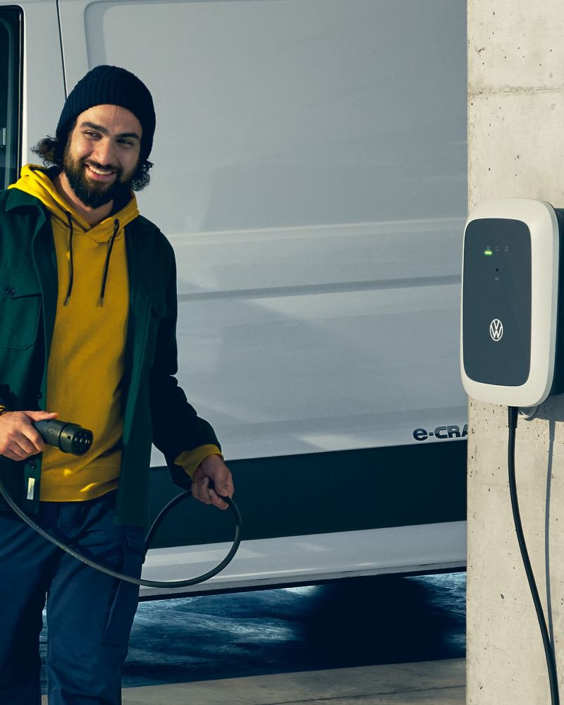 Un Volkswagen ID. Charger sur une borne en béton et un homme tenant le câble de recharge.