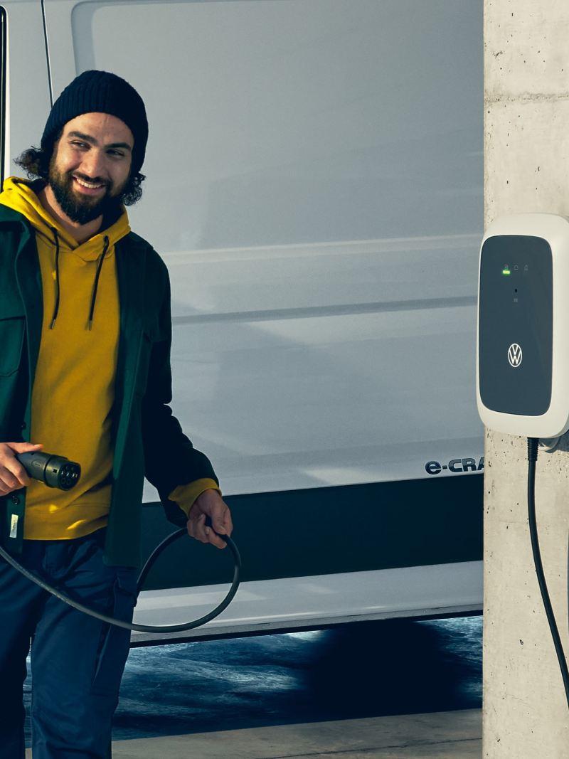 Eine Volkswagen ID. Charger an einer Betonsäule und ein Mann, der das Ladekabel hält.