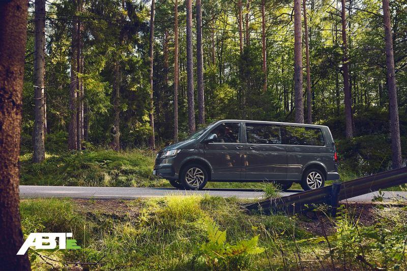 Une Volkswagen Caravelle traverse une forêt.
