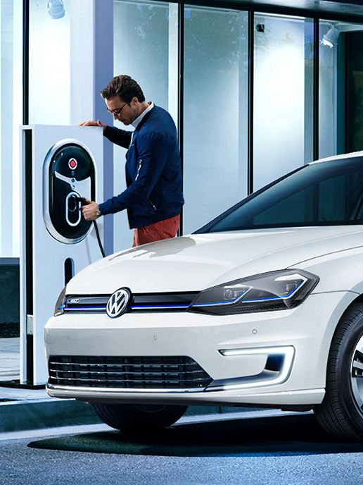 Men charging an e-golf