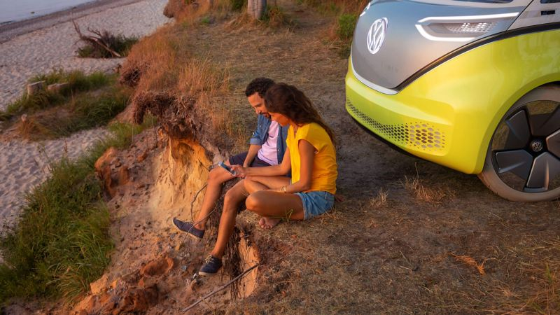 Couple sitting by Volkswagen car