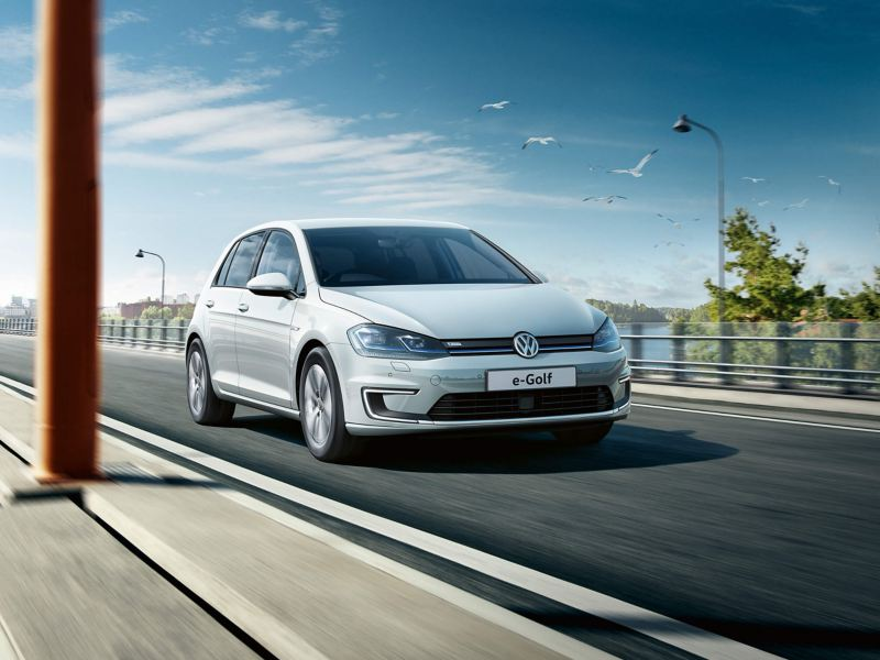 White Volkswagen e-Golf driving on the road near the sea
