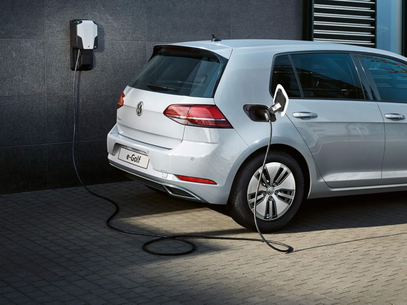 A silver Volkswagen e-Golf, charging at a wall mounted charge point.