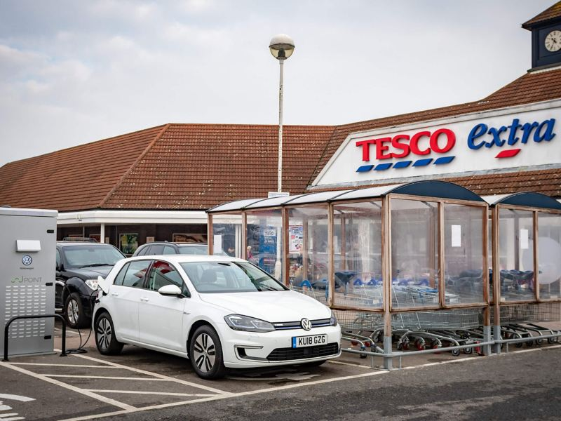 A white Volkswagen e-Golf charging in a Tesco carpark.
