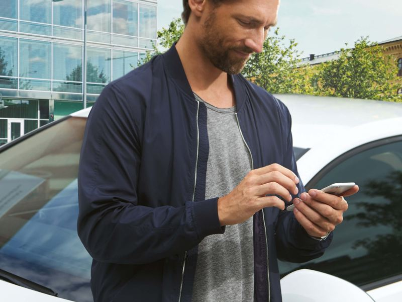 A man checking the charging app on his smart phone, next to a Volkswagen e-Golf.