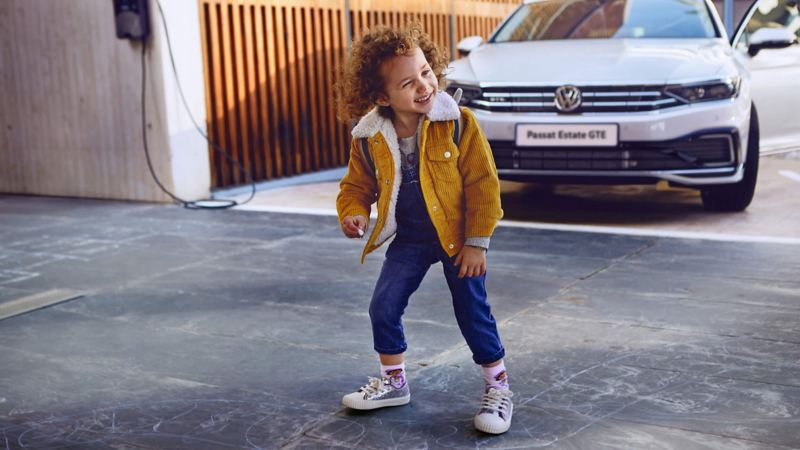 A small child in front of the Volkswagen Passat Estate GTE