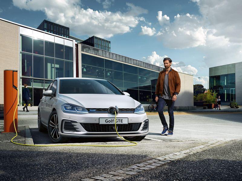 A Volkswagen Golf GTE, in a car park, charing as a man approachers.