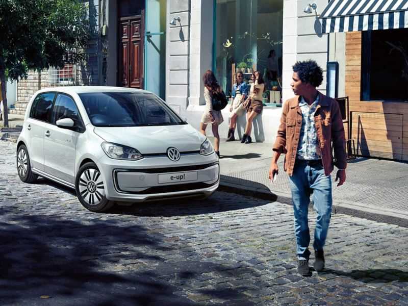 A white Volkswagen up! in a cobbled shopping street, pedestrians shopping.