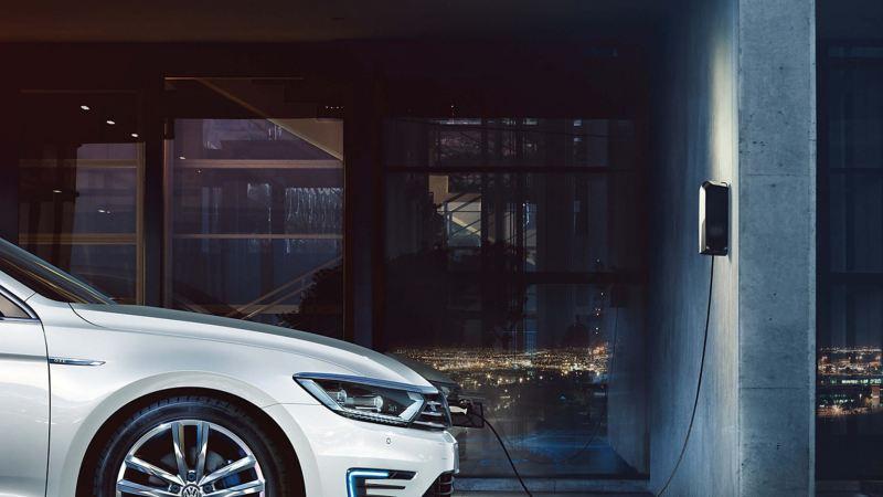 A white Volkswagen Passat Estate GTE, in a darkened space with electricity flows shown.