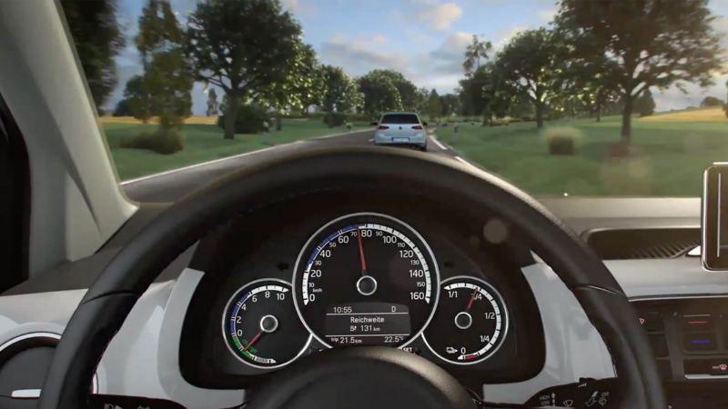 Close up of Volkswagen steering wheel, another Volkswagen e-Golf can been seen ahead.