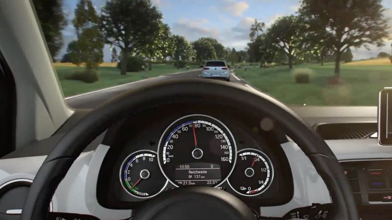 Close up of Volkswagen steering wheel, another Volkswagen e-Golf can been seen ahead.