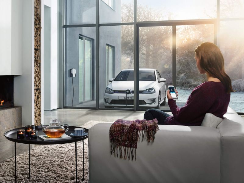 A lady at home, using her phone whilst her Volkswagen Golf GTE charges outside her window.