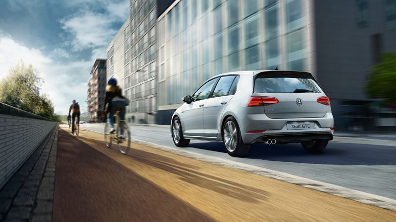 A white Volkswagen e-Golf GTE electric car driving on the road near buildings and cyclists
