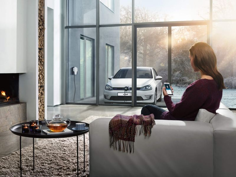 Woman looking at car from inside a room