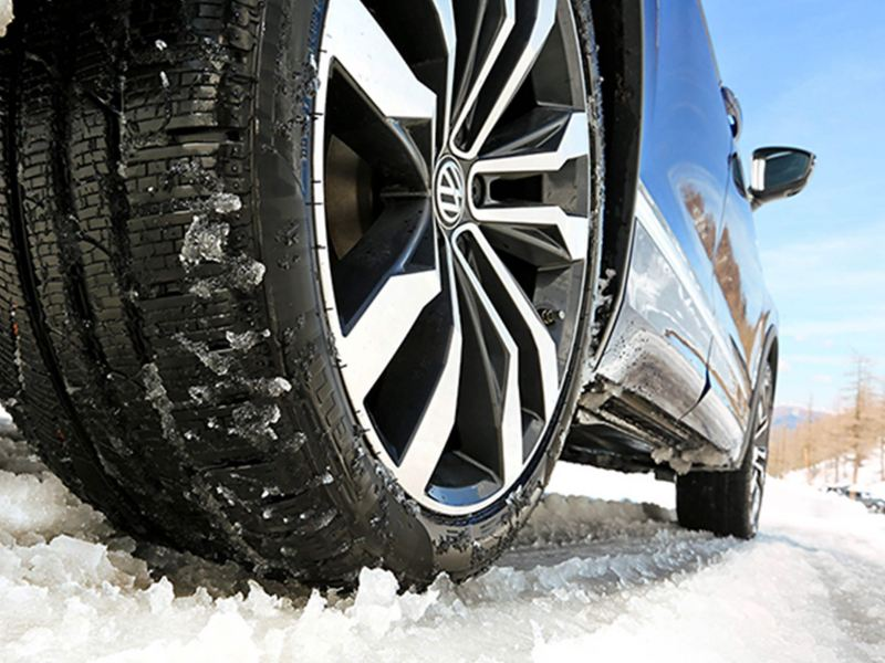 Close up of a tyre on a sunny day, in the snow.