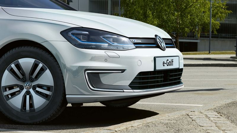 A white Volkswagen e-Golf, charging at an external charge point.