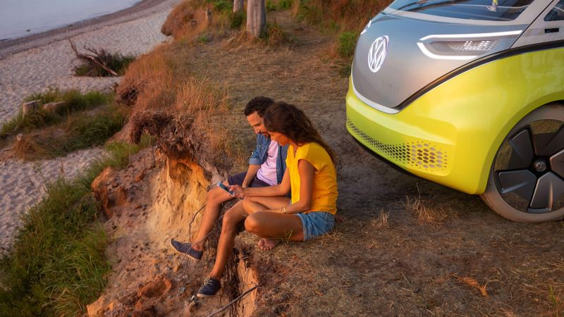 A couple sitting by a Volkswagen car