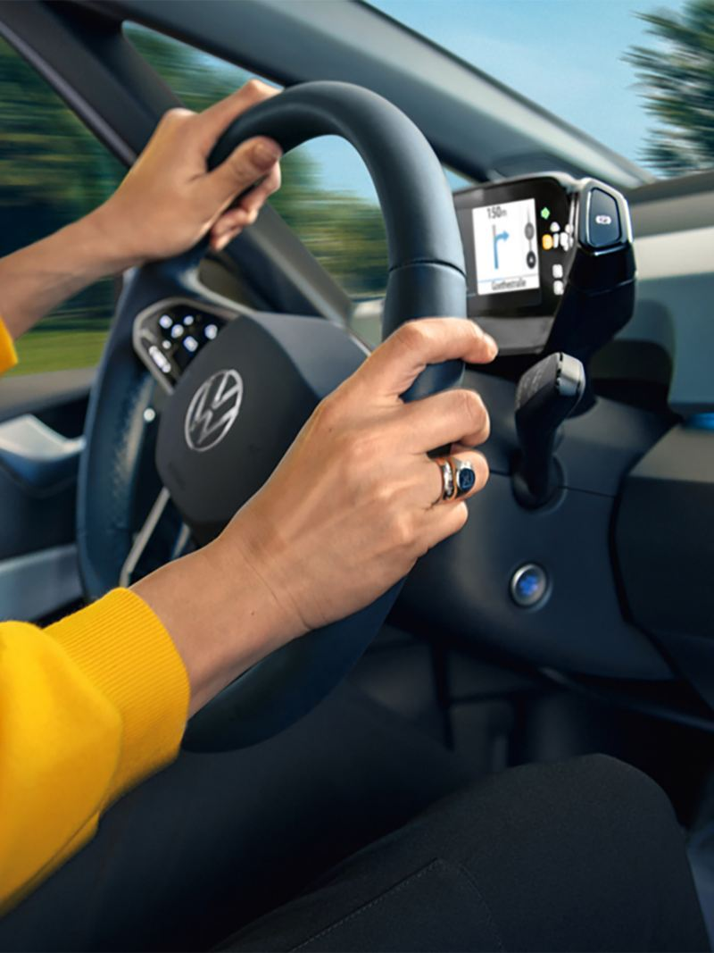 Passenger side view of a person in a yellow sweatshirt behind the wheel of a Volkswagen ID.3