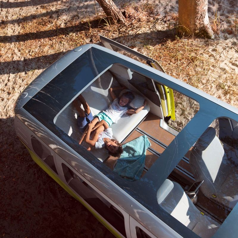 Arial shot of the Volkswagen ID. Buzz, a family seen through the open sunroof.