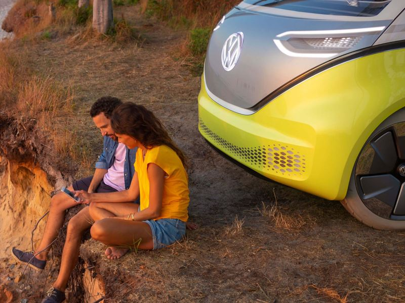 A couple sat on a cliff face over a beach, the Volkswagen ID. behind them.