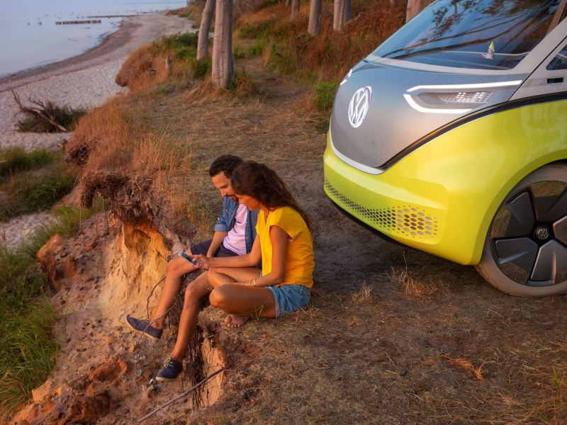 People sitting in front of a electric vehicle