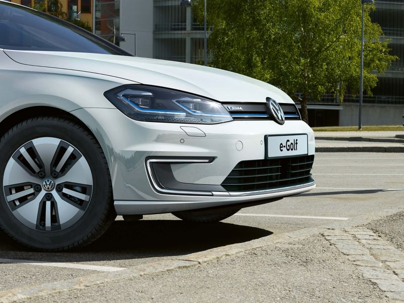 A white Volkswagen e-Golf charging in a carpark.